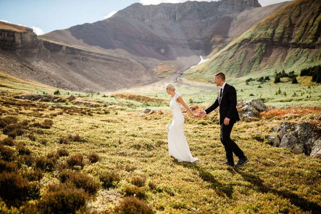 Summer elopement photograph of a bride and groom walking in the Alpine meadows