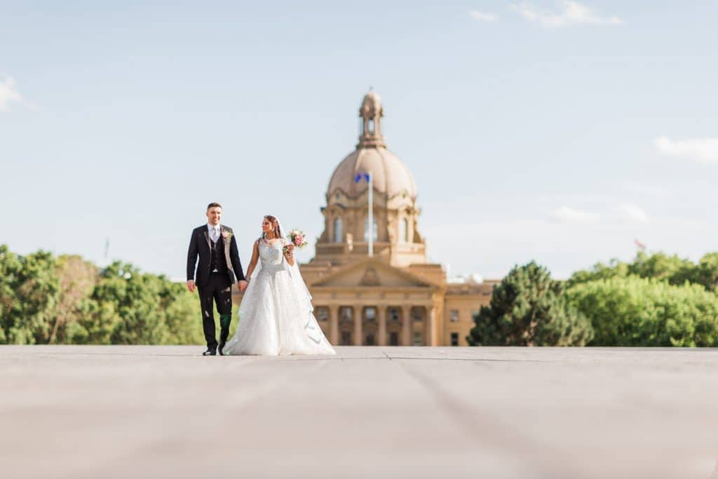 Bride and groom walking on their wedding day on the grounds of the Edmonton Legislature Building