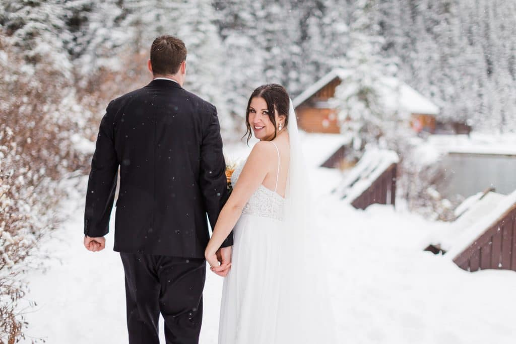 Winter wedding at Lake Louise as the bride and groom walk away towards the boat house by the Chateau