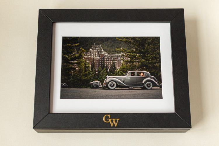 a photograph taken in Banff with a Bentley and the bride and groom inside displayed within a luxury portrait box