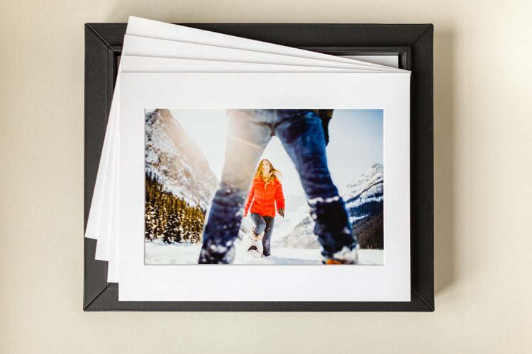 a black portrait box holding 10 matted prints of an engagement shoot taken at Lake Louise The Canadian Rockies